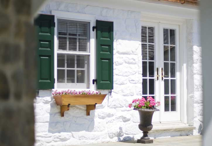 Darker shutters give contrast and character to a white stone building.