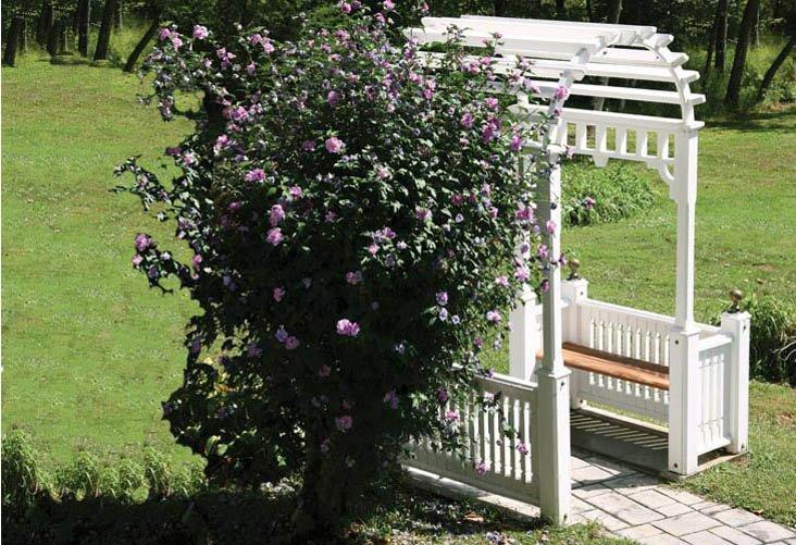 A white Vixen Hill Entrance Arbor next to a flower bush with pink flowers