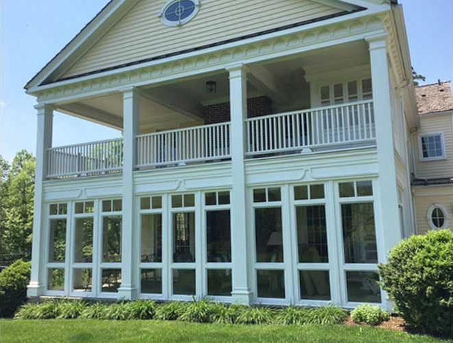 A white Vixen Hill porch system with open frame and glass inserts attached to a home below a balcony.