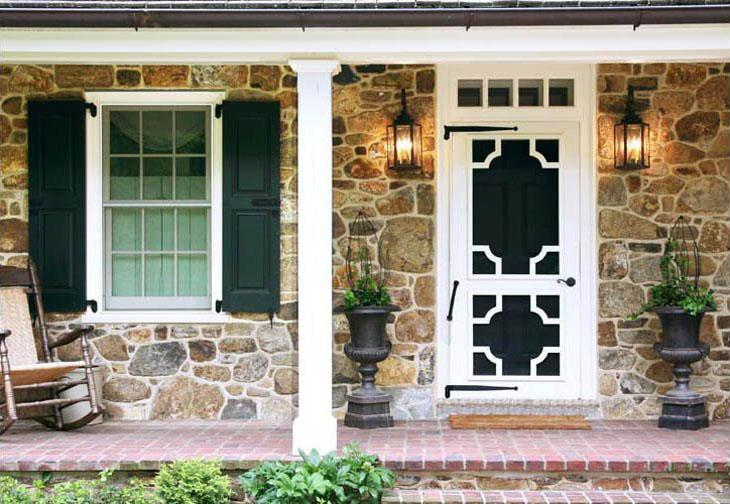 A Vixen Hill Screen door with Chippendale inserts on a stone home