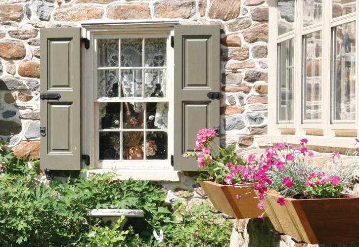 A picture of Grey Vixen Hill paneled shutters on a stone home with flower boxes.